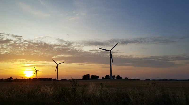 Three windmills in a flat landscape with the sun setting in the background.